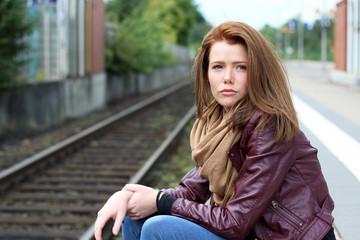 junge Frau sitzt traurig am Bahngleis