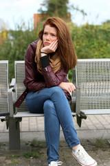 einsame, junge Frau sitzt auf einer Bank