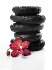 pyramid of black zen stones and red orchid, phalaenopsis on whit