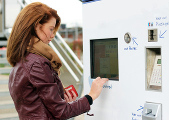 junge Frau sucht Ticket am Fahrkartenautomat
