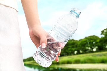 Woman carrying bottle of water in nature. Recycle.