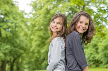 Zwei Mädchen lachend Rücken an Rücken