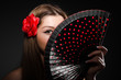 Beautiful young woman with flower and fan