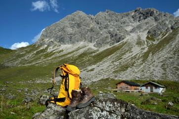 Rucksack und Bergschuhe vor Berghütte