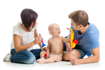 Mother, father and baby boy play musical toys. Isolated on white