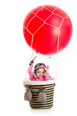 child with pilot hat and teleskop on hot air balloon