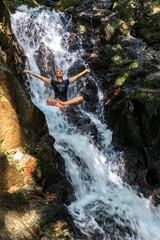 Young woman enjoying waterfall freshness