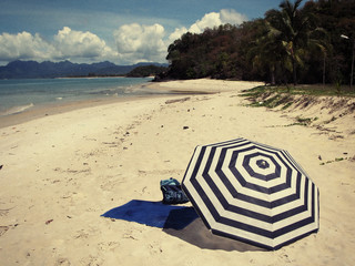 Striped umbrella on a secluded beach of Langkawi island, Malaysi