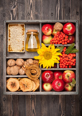 Autumn Collage in wooden box. Apples, honey, nuts, sunflower.