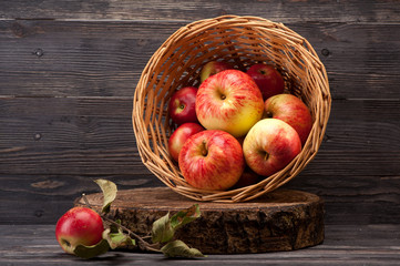 Red apples in a basket on wooden textured board