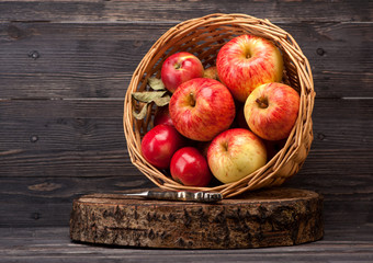 Red apples in basket on wooden textured board