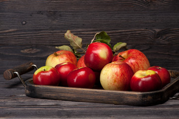 Red apples and wooden tray