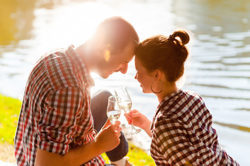 Man and woman clanging wine glasses with champagne
