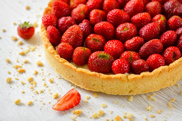 Strawberry tart on white wooden background