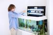 Child putting new fish in an aquarium