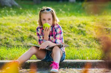 Little girl sitting on the street eating an apple.