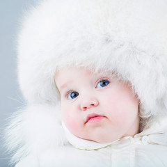 Very funny baby in a white snow suit and big fur hat