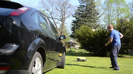 Car automobile washing with strong water jet on garden lawn
