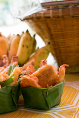 Thai deep fried sliced banana in leave vessel and bamboo basket