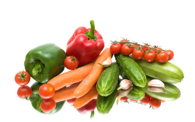 Vegetables on the mirror surface. white background.