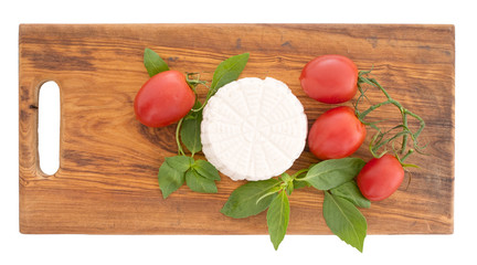 Fresh ricotta cheese with herb basil and tomatoes on rustic wood