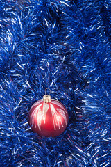 Red Christmas ball on the background of blue tinsel