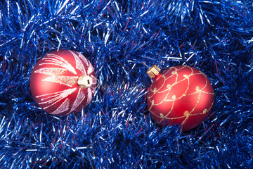 Red Christmas balls on the background of blue tinsel