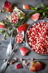 pomegranate grains on bowl with two silver spoon full of grains