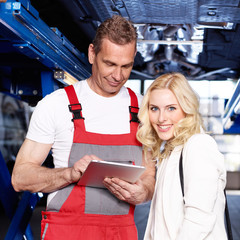 Female customer and mechanic in a garage