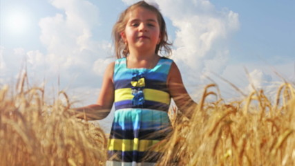 Little girl running through a wheat field