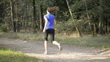 Athletic young woman jogging along a forest track