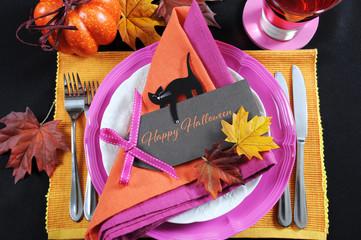 Bright, modern pink, orange and black Halloween table setting