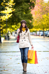 Woman walking with shopping bags in autumn