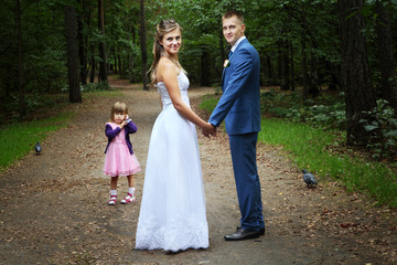 Wedding walk, newlyweds with child walking in forest.