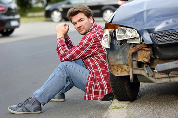 Man sitting near the car after accident