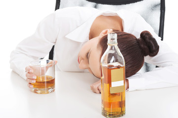 Alone young businesswoman drinking alcohol
