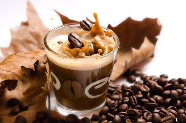 tazza di caffe espresso, con foglie secche e chicchi di caffe