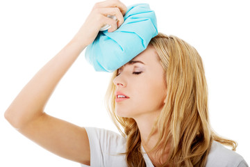 Woman with ice bag, having headache.