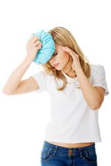 Woman with ice bag, having headache.