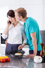 Husband kissing his wife during breakfast preparation