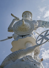 Frontal and low view of a statue of Saint Michael