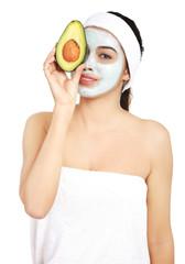 Beautiful spa woman in facial mask and avocado