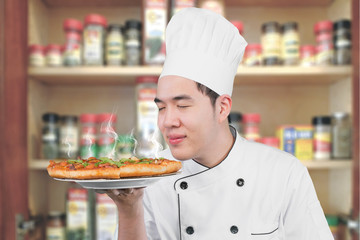 Chef smelling pizza in the kitchen