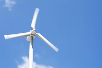 回転中の風力発電の模型と青空