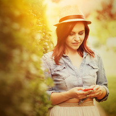 Redhead hipster young woman outdoors with smart phone texting