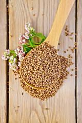 Buckwheat in spoon with flower on board
