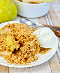 Crumble with pears in bowl on linen tablecloth