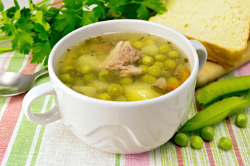 Soup from green peas with meat on napkin