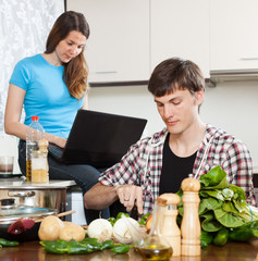 Man preparing food while woman looking at laptop
