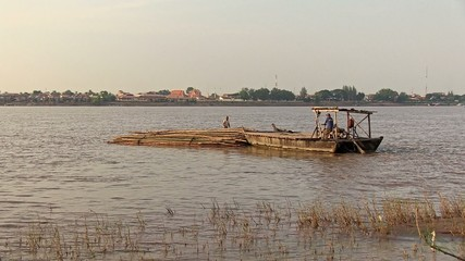 A bamboo raft is towed by small boat